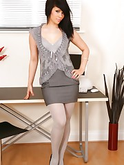 Laura wearing an all grey secretary outfit with light grey..