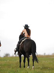 Brunette model Kristina rides a black horse