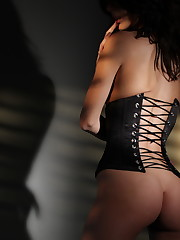 is a wild brunette with black fishnets and a corset