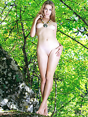 Genevieve Gandi playfully poses in the forest as she bares..