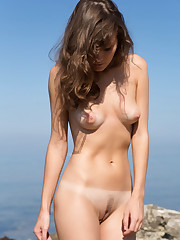 New model Carmela bares her tanned body as she poses by..