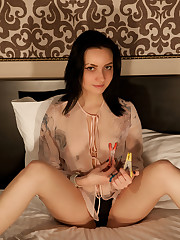 Zara D strips on the bed as she play with her pussy.