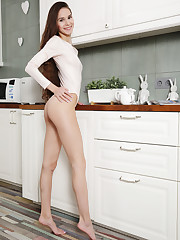 Leona Mia bares her slim body and pink pussy in the kitchen.