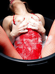 Marlyn wearing hot red lingerie and matching fishnet..