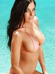 Alluring Vixen De is poolside in a very tiny string bikini..