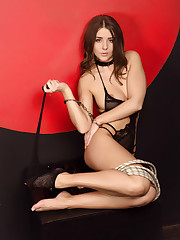 Sybil A poses in sheer black lingerie, handcuff, and rope.