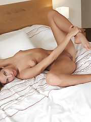 Antea sensually poses on the bed baring her erect nipples..