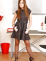 Brunette Cate wearing a patterned minidress in her office.