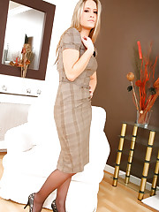 Beautiful blonde in smart checkered dress and light..